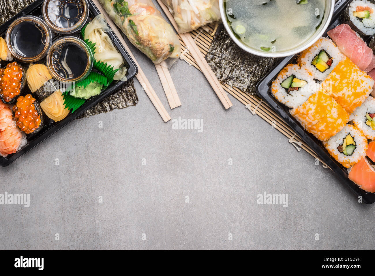 Sushi menu with summer rolls in rice paper wrappers and miso soup on gray  stone background, top view, border.  - Stock Image