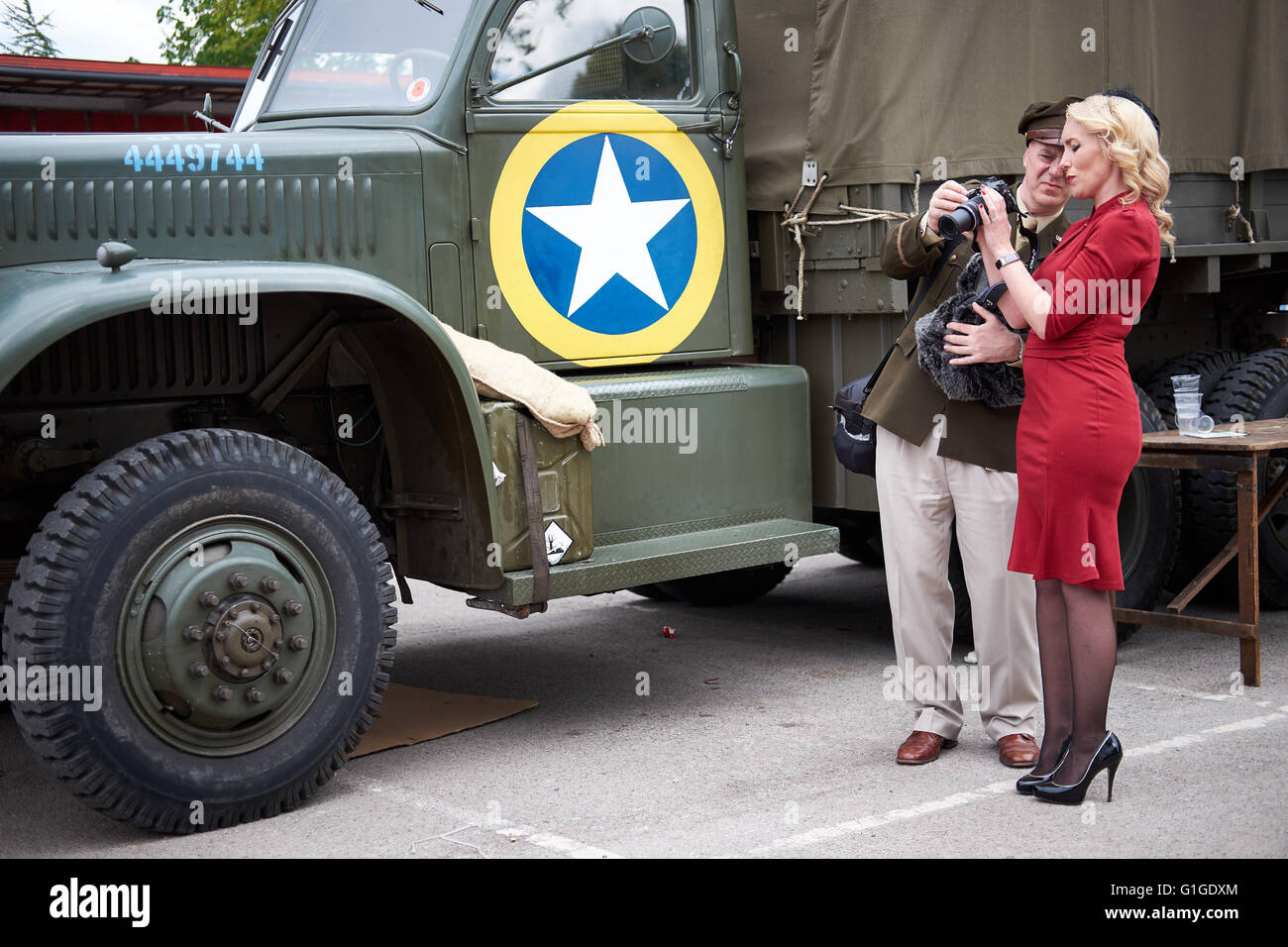 Man dressed in vintage soldier US military uniform shows camera to blonde woman dressed in red dress with black - Stock Image