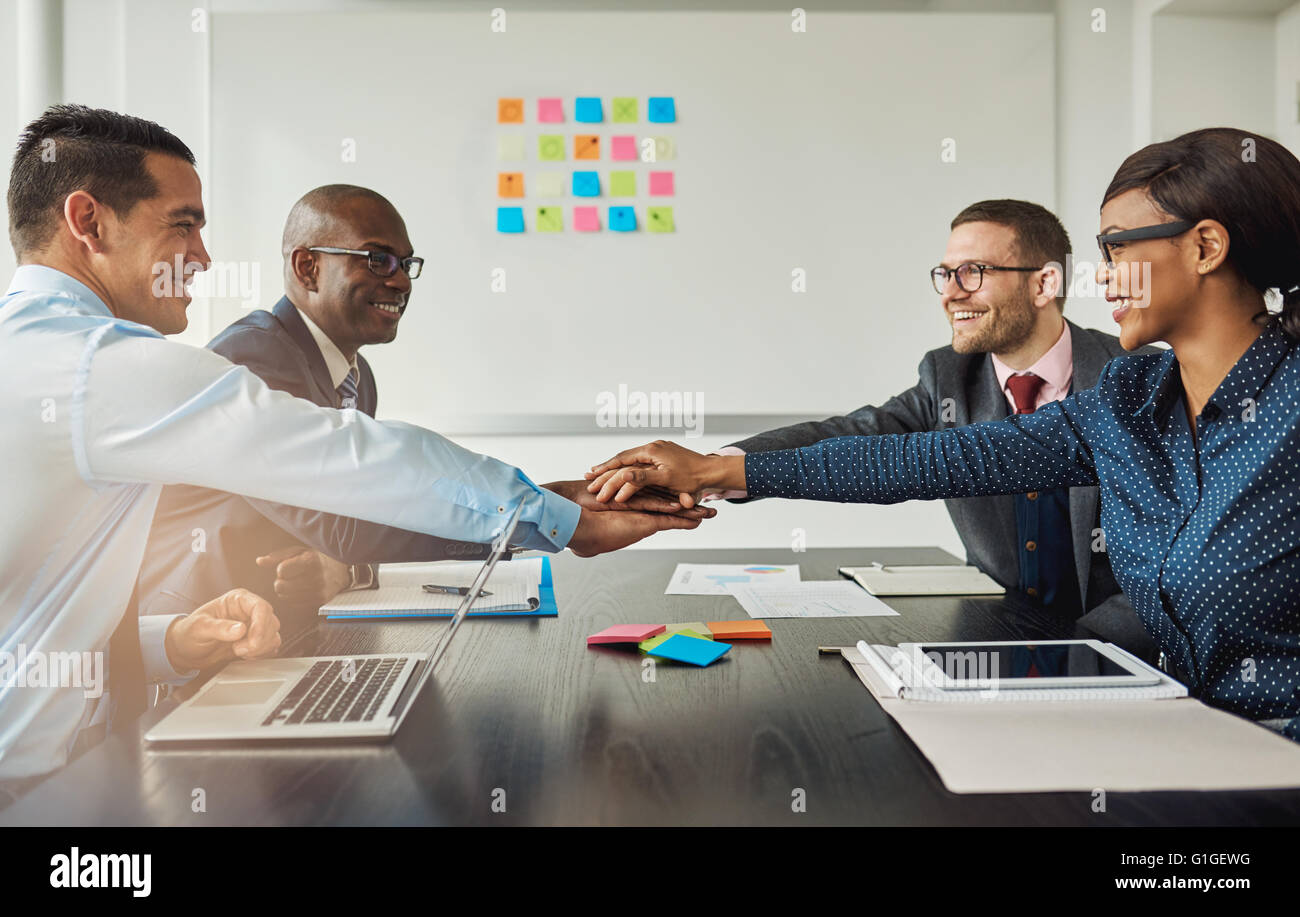 Multiracial business team signalling their commitment to each other by reaching across the table in the office to - Stock Image