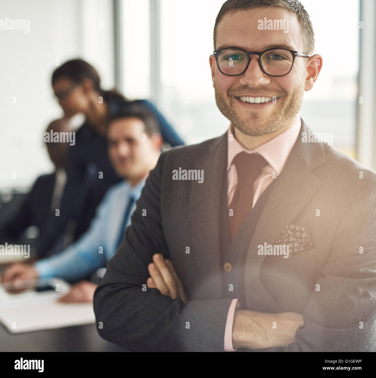 Smiling confident businessman wearing glasses standing with folded arms looking at the camera, close up view with - Stock Image