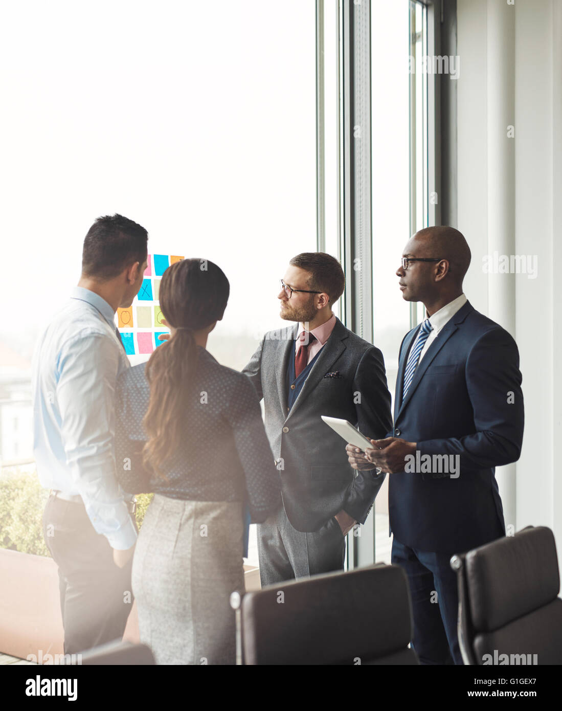 Multiracial business team having a meeting discussing their strategy and ideas for a new project as they stand in Stock Photo