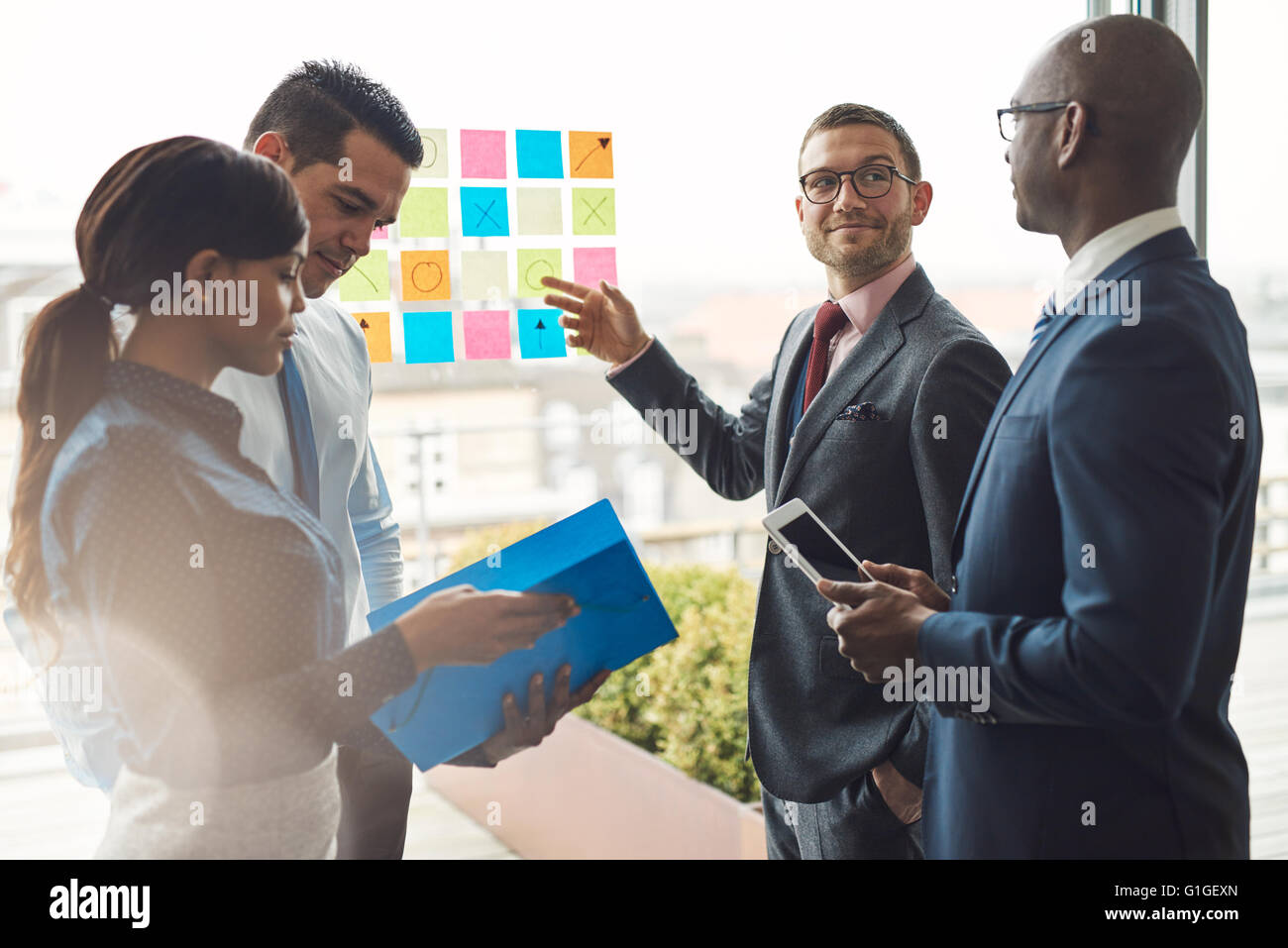 Young group of diverse business people in conference meeting using colorful sticky notes to organize ideas on large - Stock Image