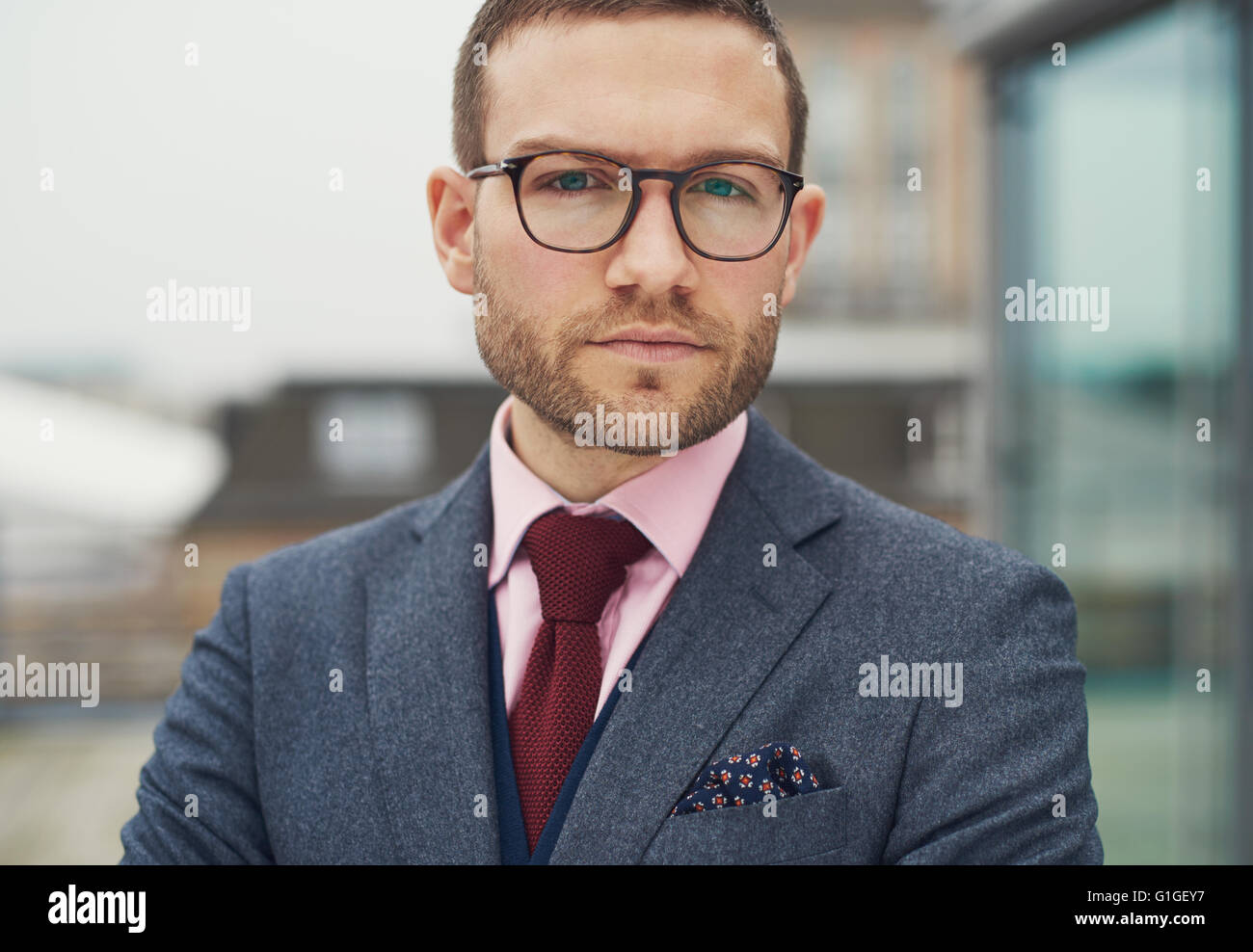 Thoughtful businessman staring intently at the camera with a serious inscrutable expression, close up cropped head - Stock Image