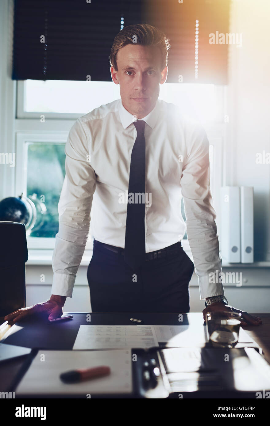 Executive business man standing at desk at office with hands resting at desk looking serious at camera - Stock Image