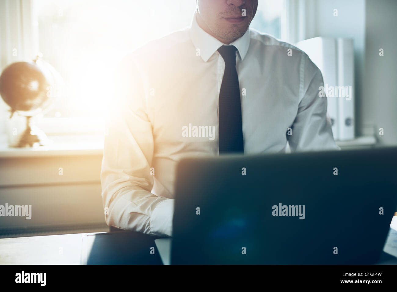 Close up of business man working at laptop, white shirt and tie business concept - Stock Image