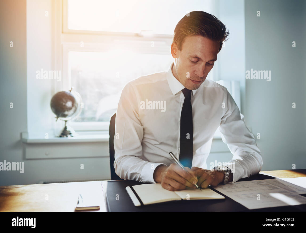 Executive business man working at office writing in a calendar and looking seriously - Stock Image