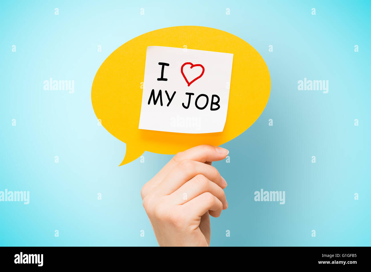 "Adhesive note on yellow speech bubble with ""I love my job"" words on blue background. Stock Photo"
