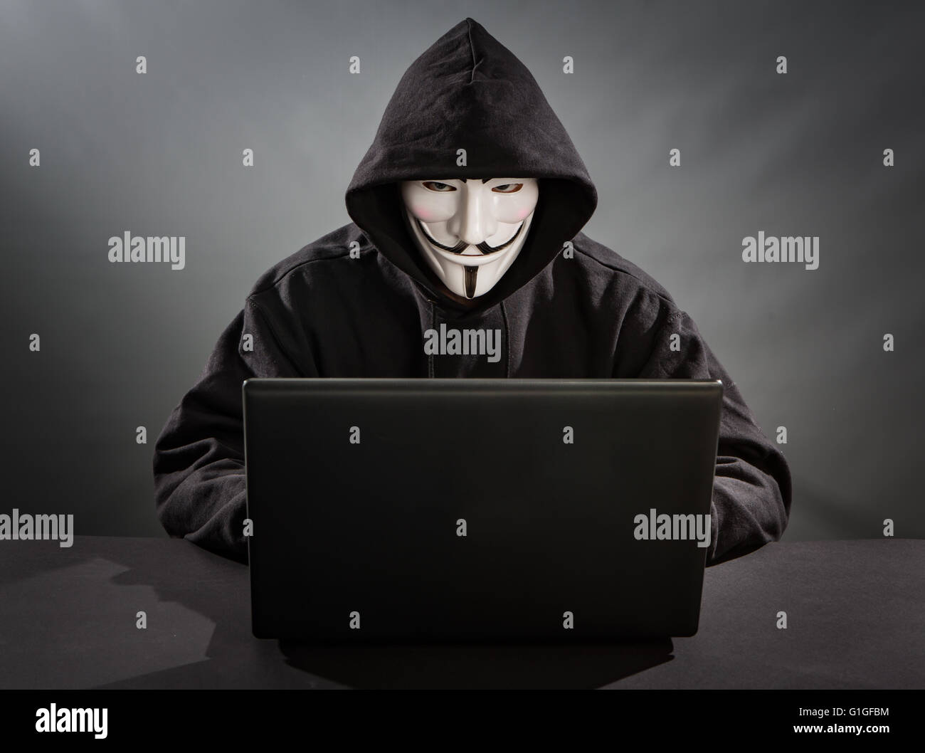 Bełchatow, Poland - December 18, 2015: Man with the laptop wearing Vendetta mask - symbol for the online hacktivist - Stock Image