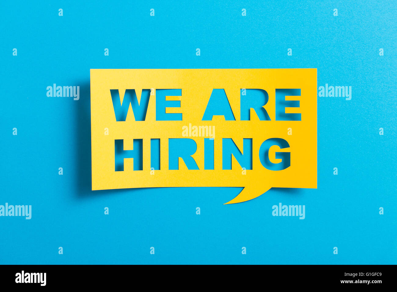 Bubble speech with cut out phrase 'we are hiring'  in the paper. - Stock Image