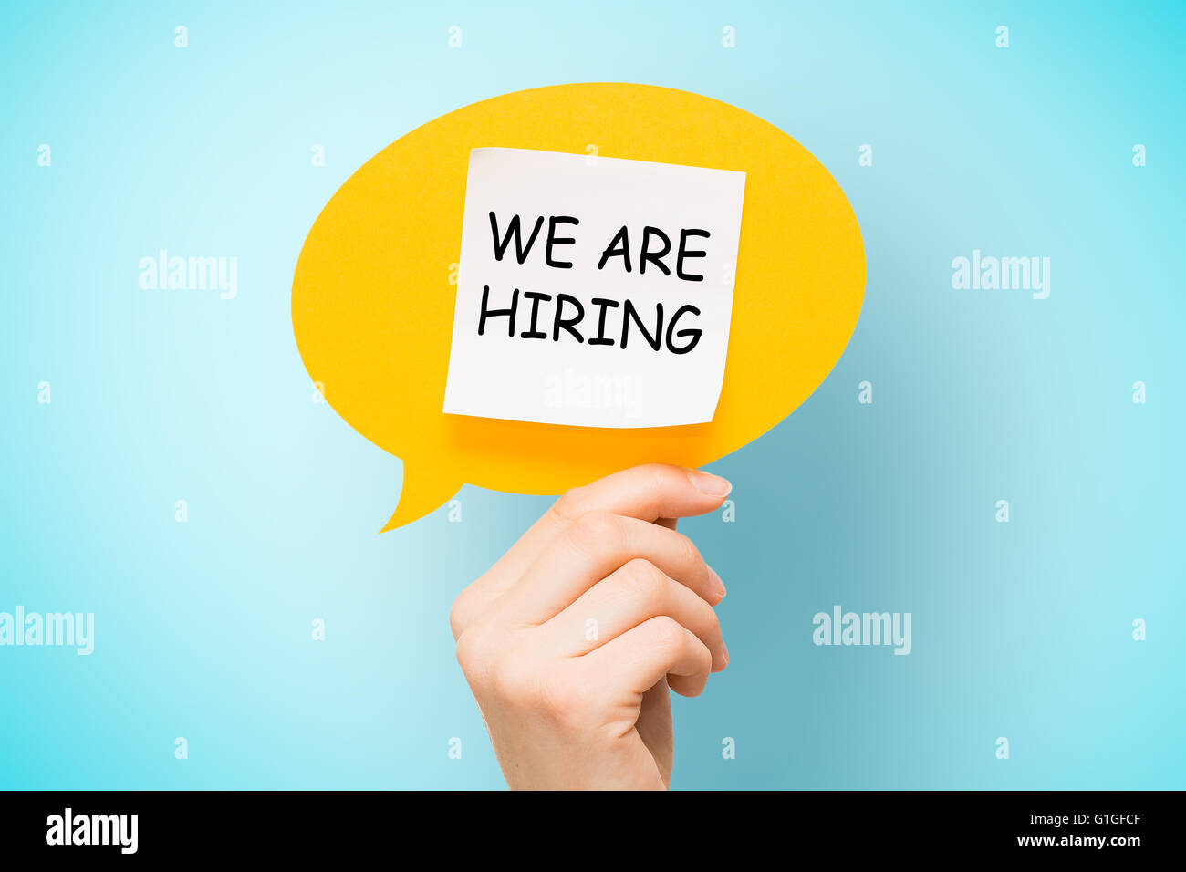 Adhesive note on yellow speech bubble with 'we are hiring' words on blue background. - Stock Image