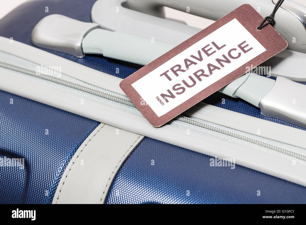 Travel insurance label tied to a suitcase. - Stock Image