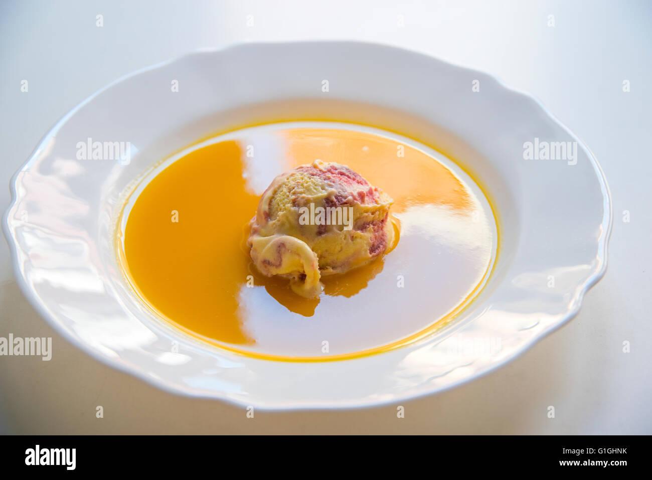 Mango and raspberry ice cream in mango soup. - Stock Image