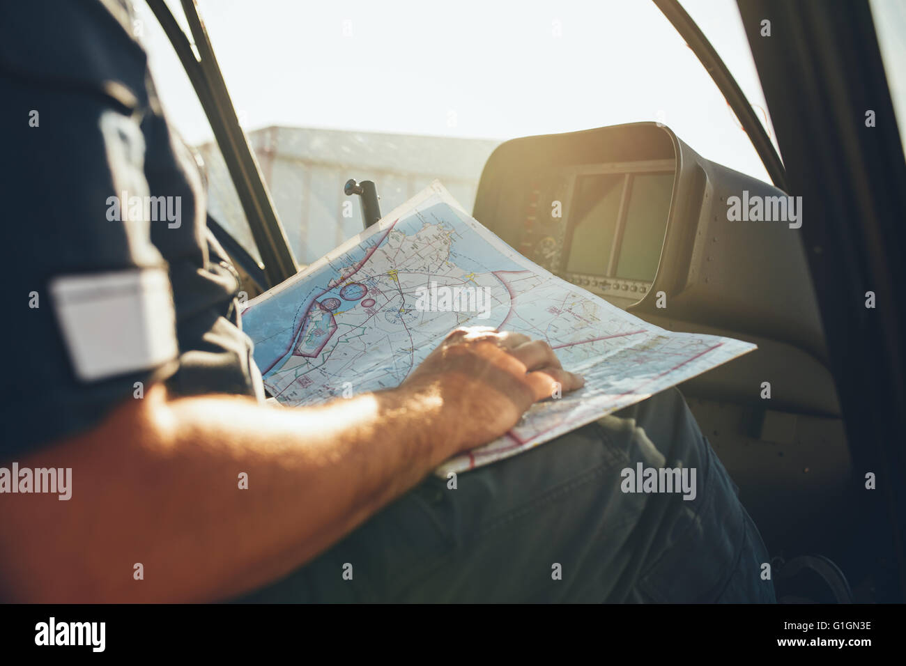 Close up shot of a helicopter pilot studying the flight route map while sitting in the cockpit of the aircraft. - Stock Image