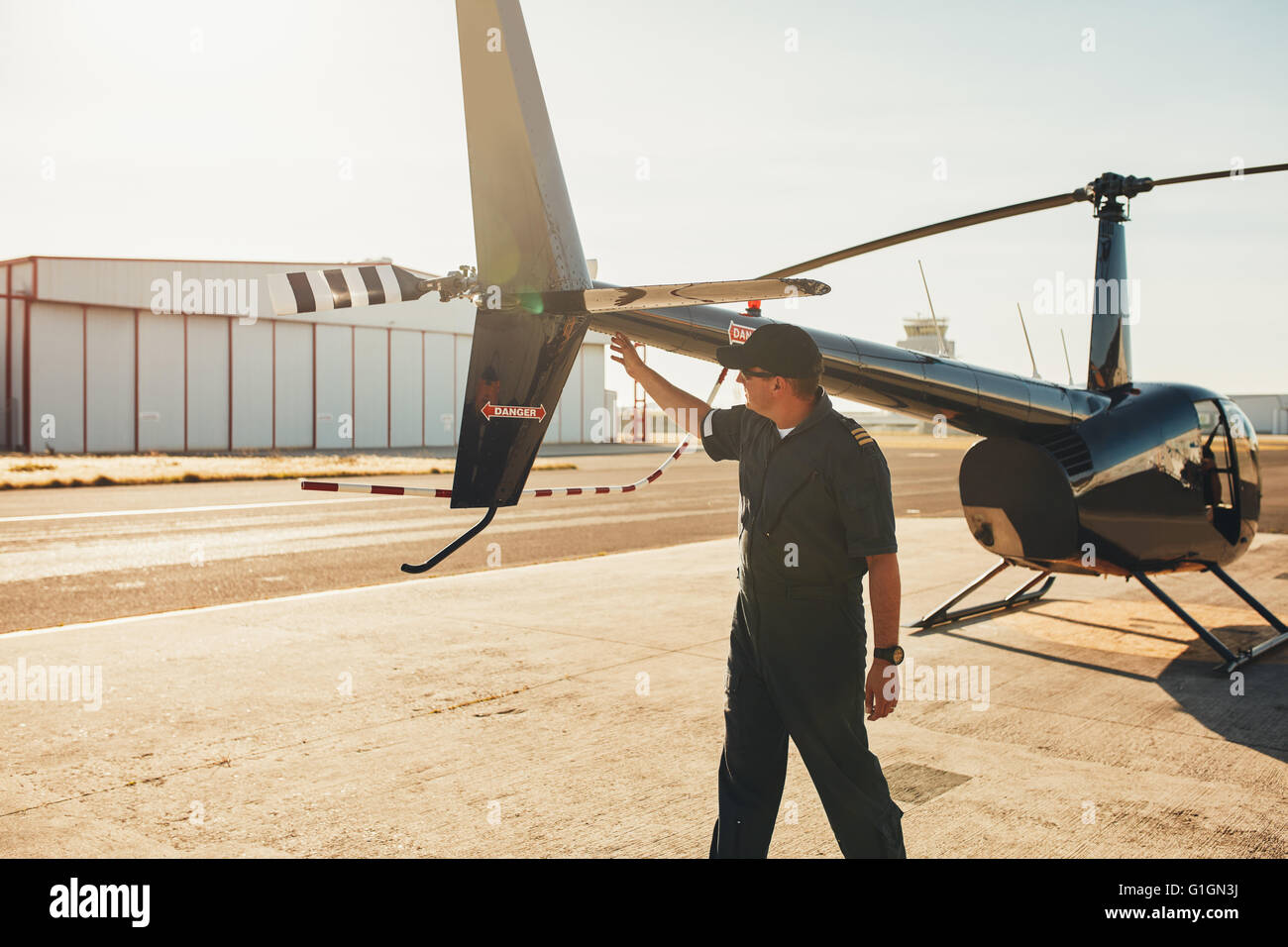 Pilot checking tail wings helicopter during preflight checklist on a sunny day. Engineer doing pre flight inspection. - Stock Image
