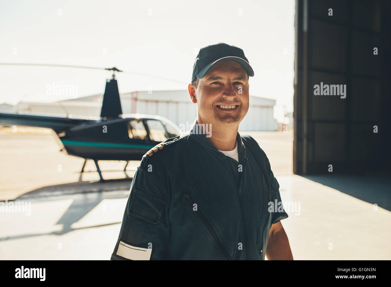 Portrait of happy male pilot standing in airplane hangar with a helicopter in background - Stock Image