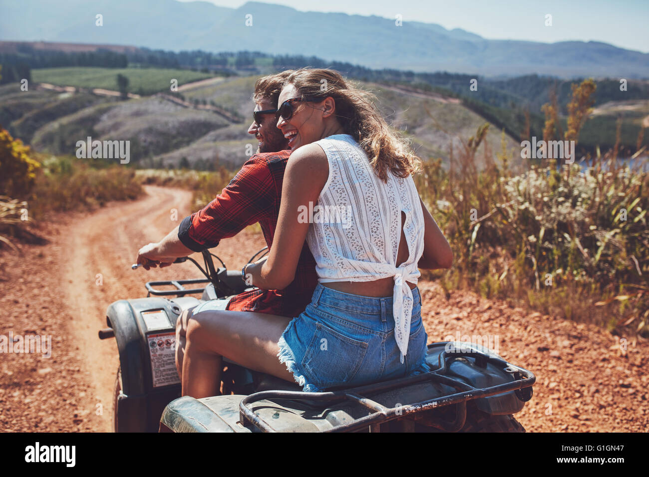 Rear view shot of young couple riding on a quad bike in countryside and looking away smiling. Woman sitting behind - Stock Image