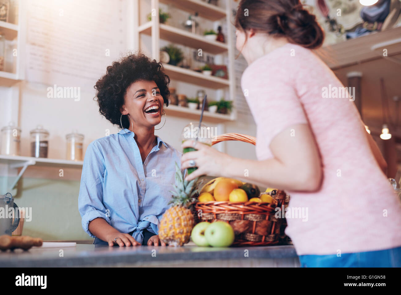 Portrait of young african woman standing behind juice bar counter and talking with female customer holding a glass - Stock Image