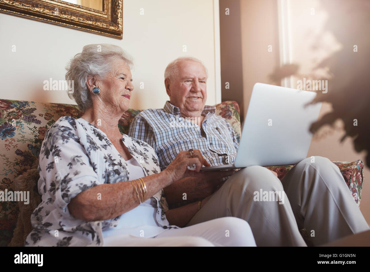 Elderly couple using laptop computer at home. Senior man and woman sitting on sofa working on laptop. - Stock Image