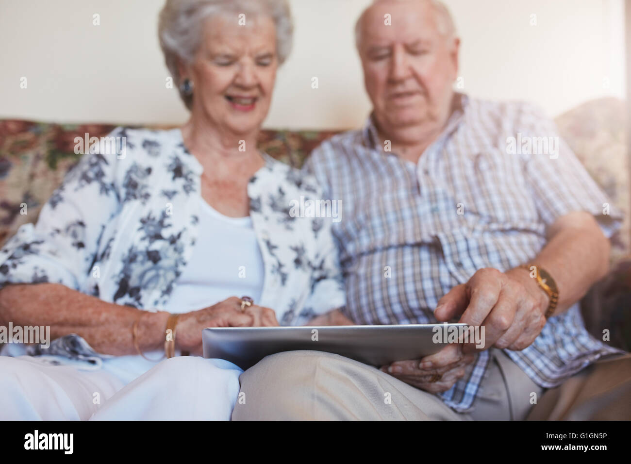 Portrait of happy senior couple sitting together at home and using digital tablet. Elderly man and woman sitting - Stock Image