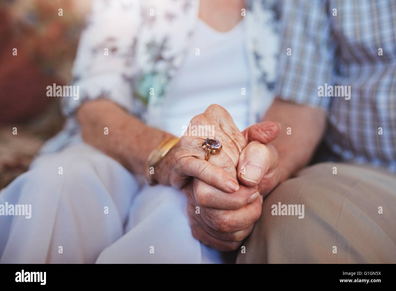 Cropped shot of elderly couple holding hands while sitting together at home. Focus on hands. - Stock Image