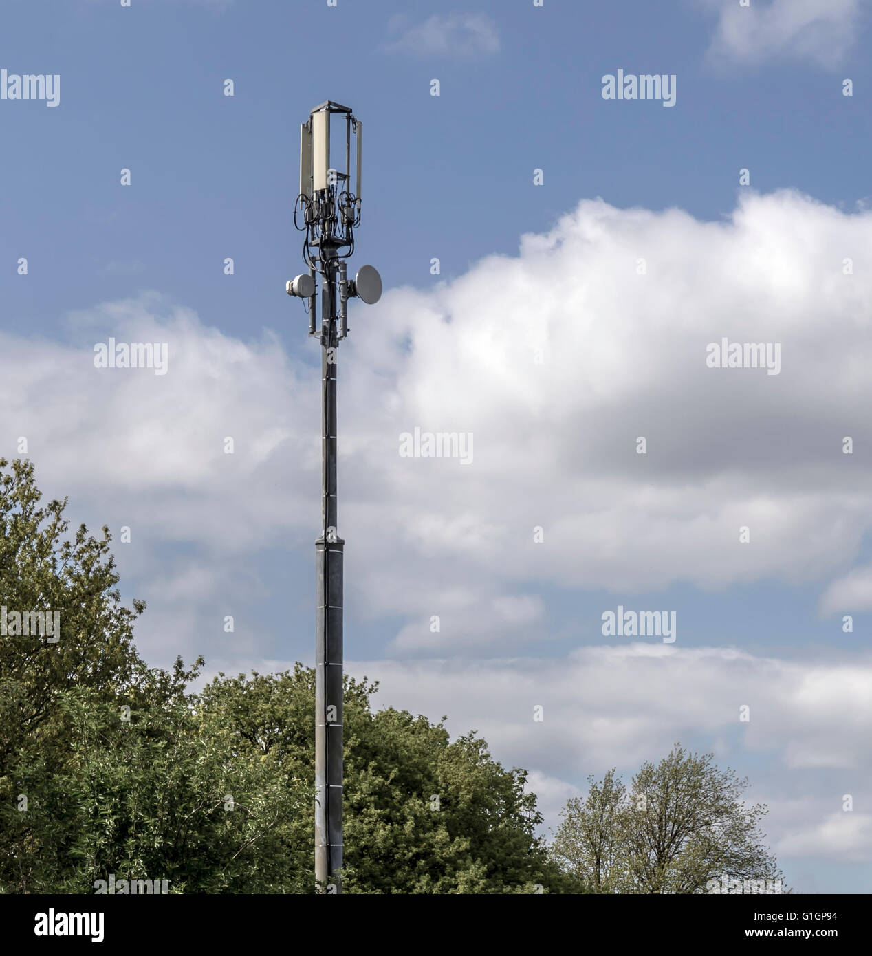 Mobile Telephone Communications Tower against blue sky and trees - Stock Image