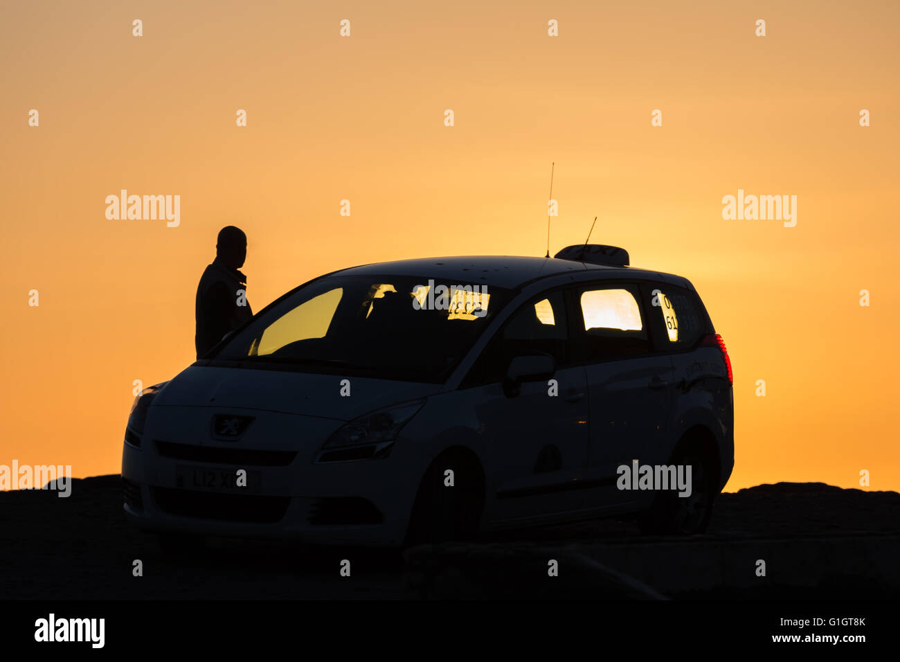 Clarach, Ceredigion, Wales, UK 14th May 2016. UK Weather: Taxi driver parks to watch a Gorgeous sunset on the west - Stock Image