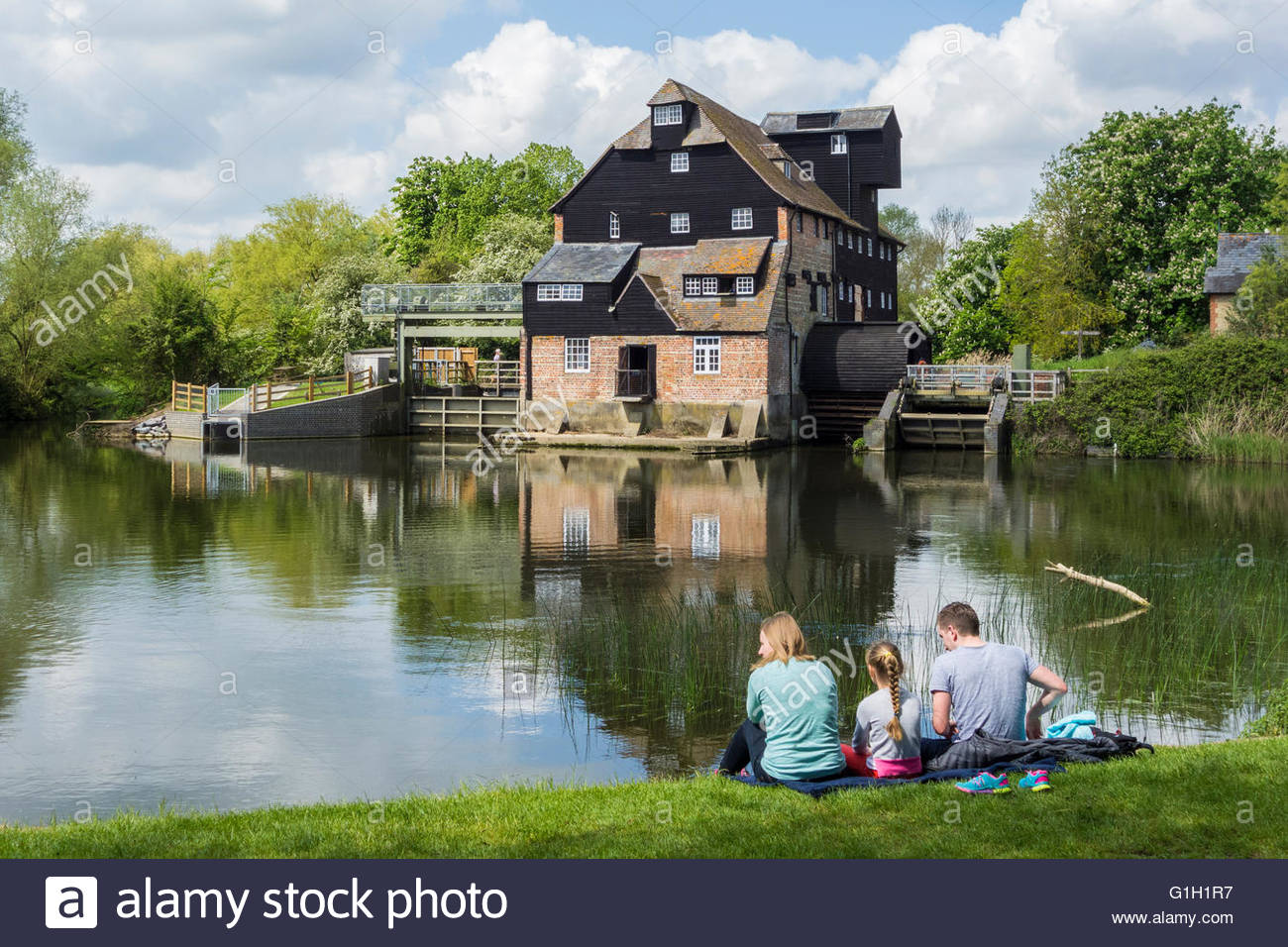 Houghton, Cambridgeshire, UK. 15 May 2016. Visitors relax in the sunshine on the bank of the River Great Ouse at - Stock Image