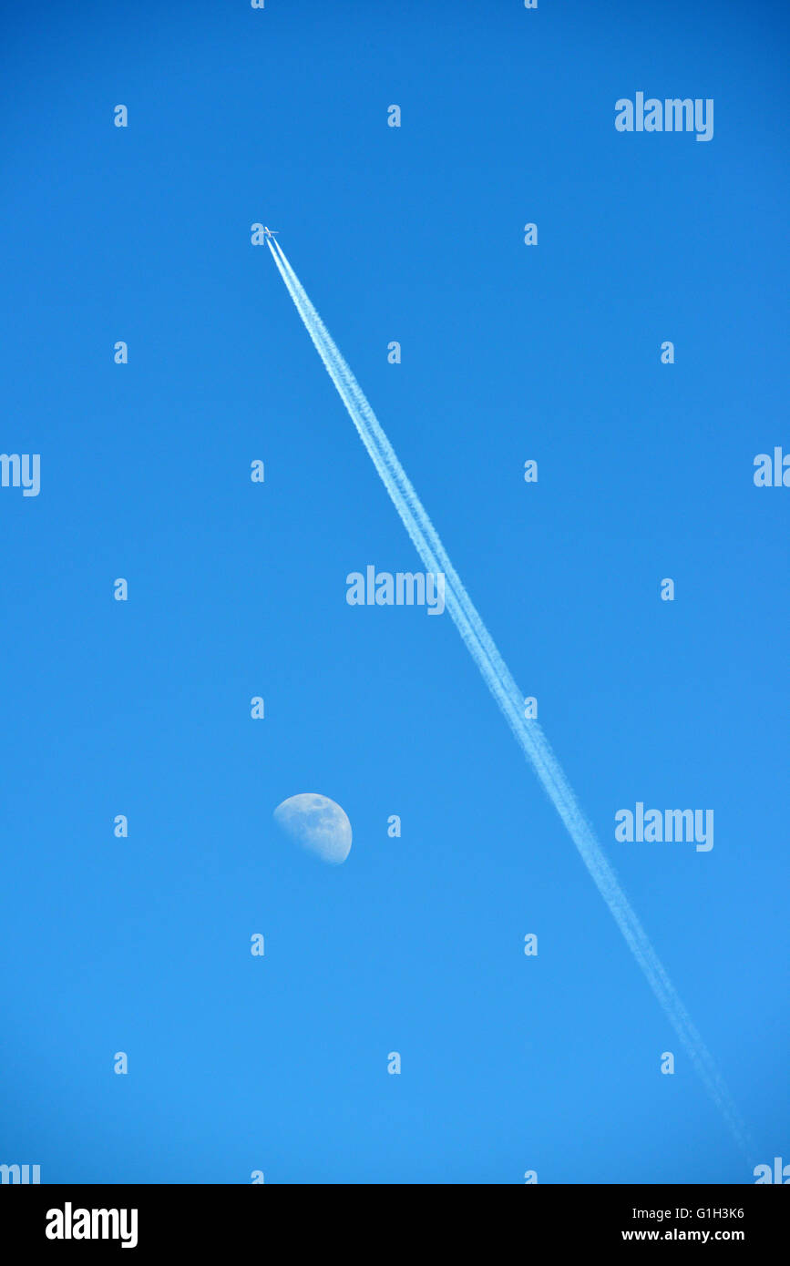 Aberystwyth, Wales, UK. 15th May, 2016. UK Weather - A twin engined airliner leaves a trail past the Moon across - Stock Image