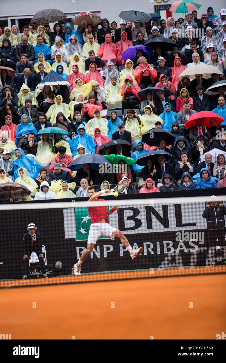 crowd carry umbrellas and wear ponchos during a shower in the BNL Rome International final between Novak Djokovic - Stock Image
