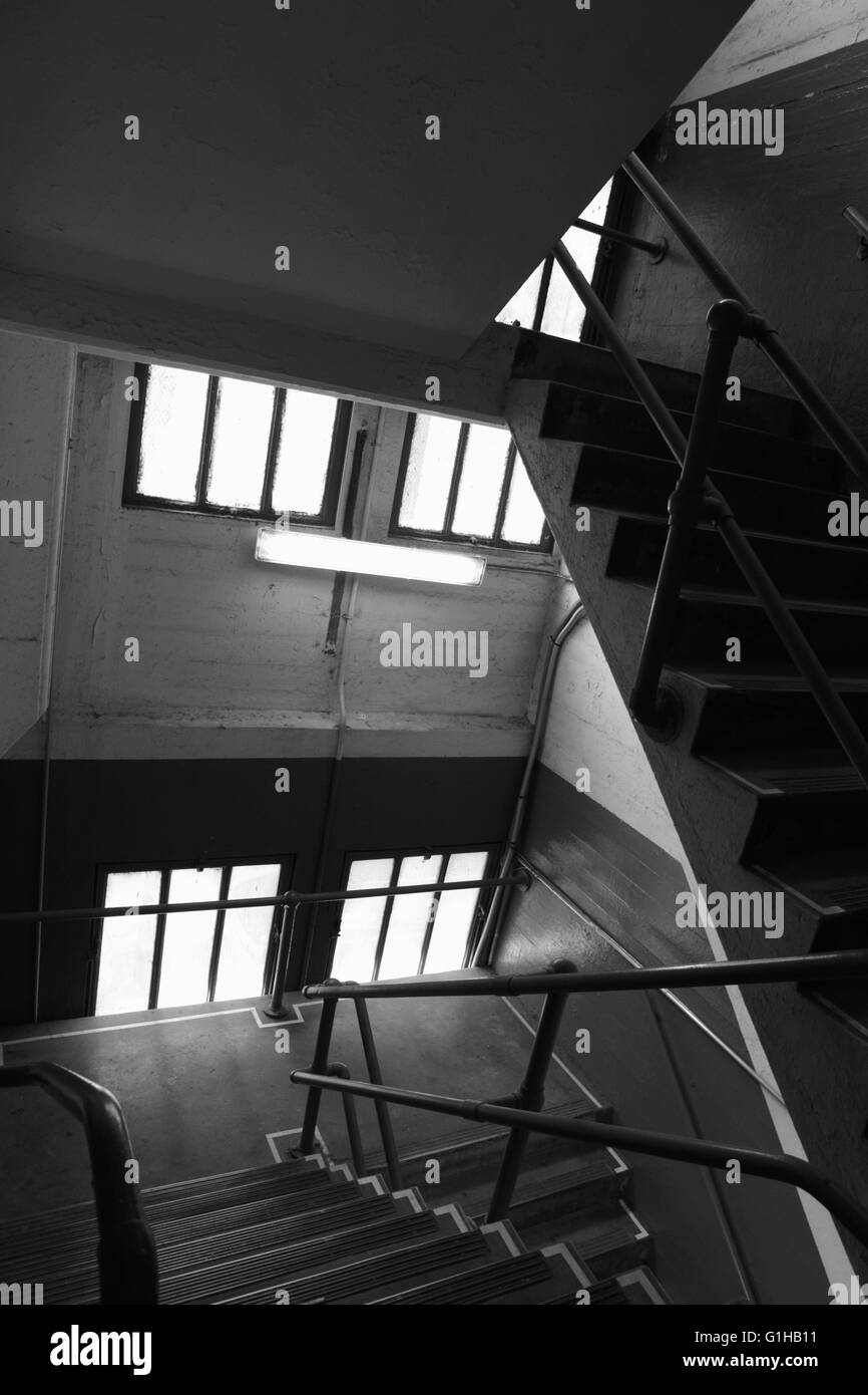 Stairwell in an old concrete industrial building with windows, stairs, and railings, shadows, and perspective - Stock Image