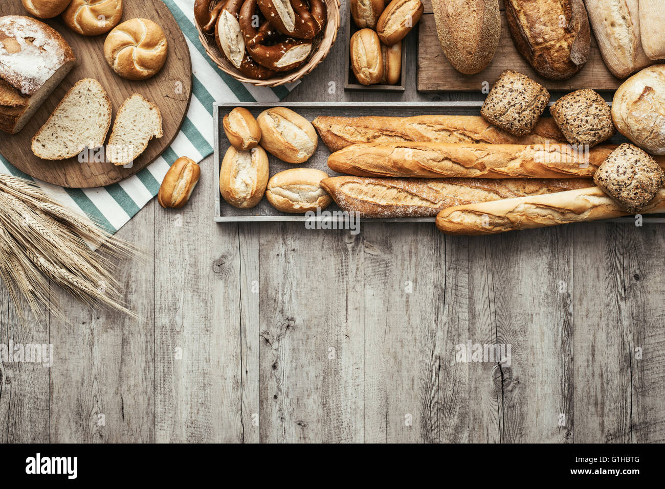 Freshly baked delicious bread on a rustic wooden worktop with copy space, healthy eating concept, flat lay - Stock Image
