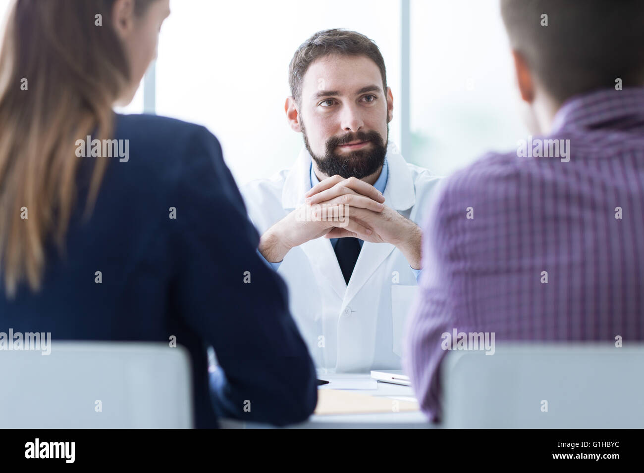 Young couple at the doctor's office during a visit, medical advice and consultation concept - Stock Image