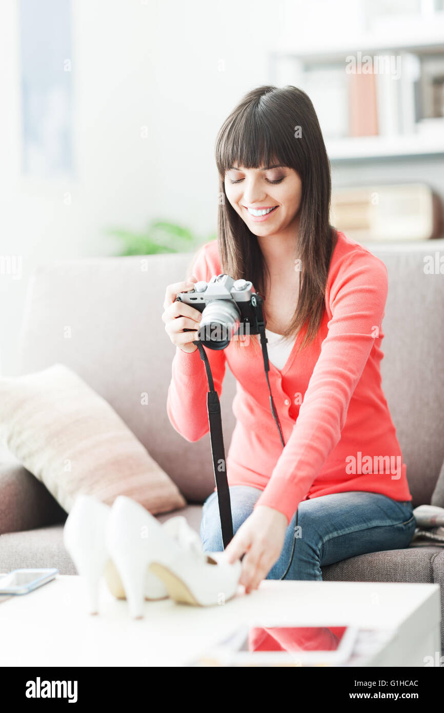 Young smiling woman taking a picture of her shoes with a camera, she is going to sell them on an online store - Stock Image