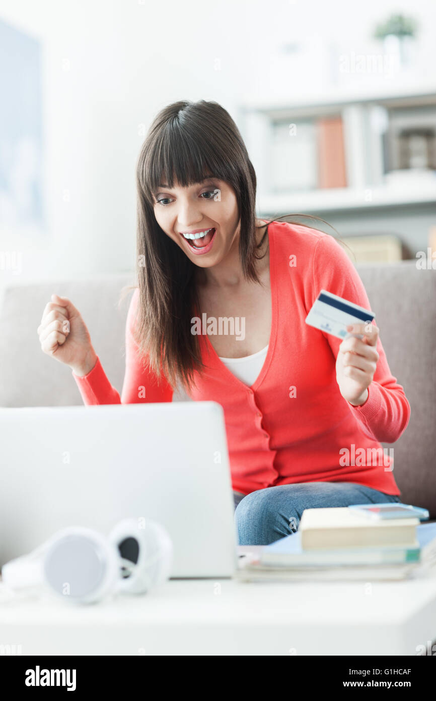 Young smiling woman at home using a laptop and shopping online with a credit card, she is cheerful with a fist raised - Stock Image