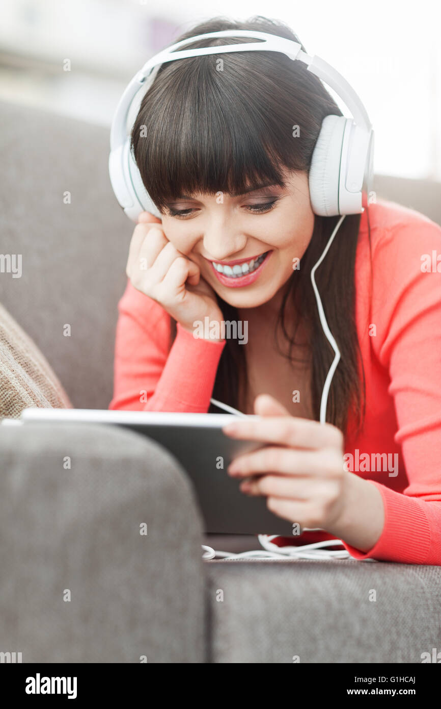 Smiling young woman relaxing at home on the couch, she is wearing headphones, using a digital tablet and watching - Stock Image