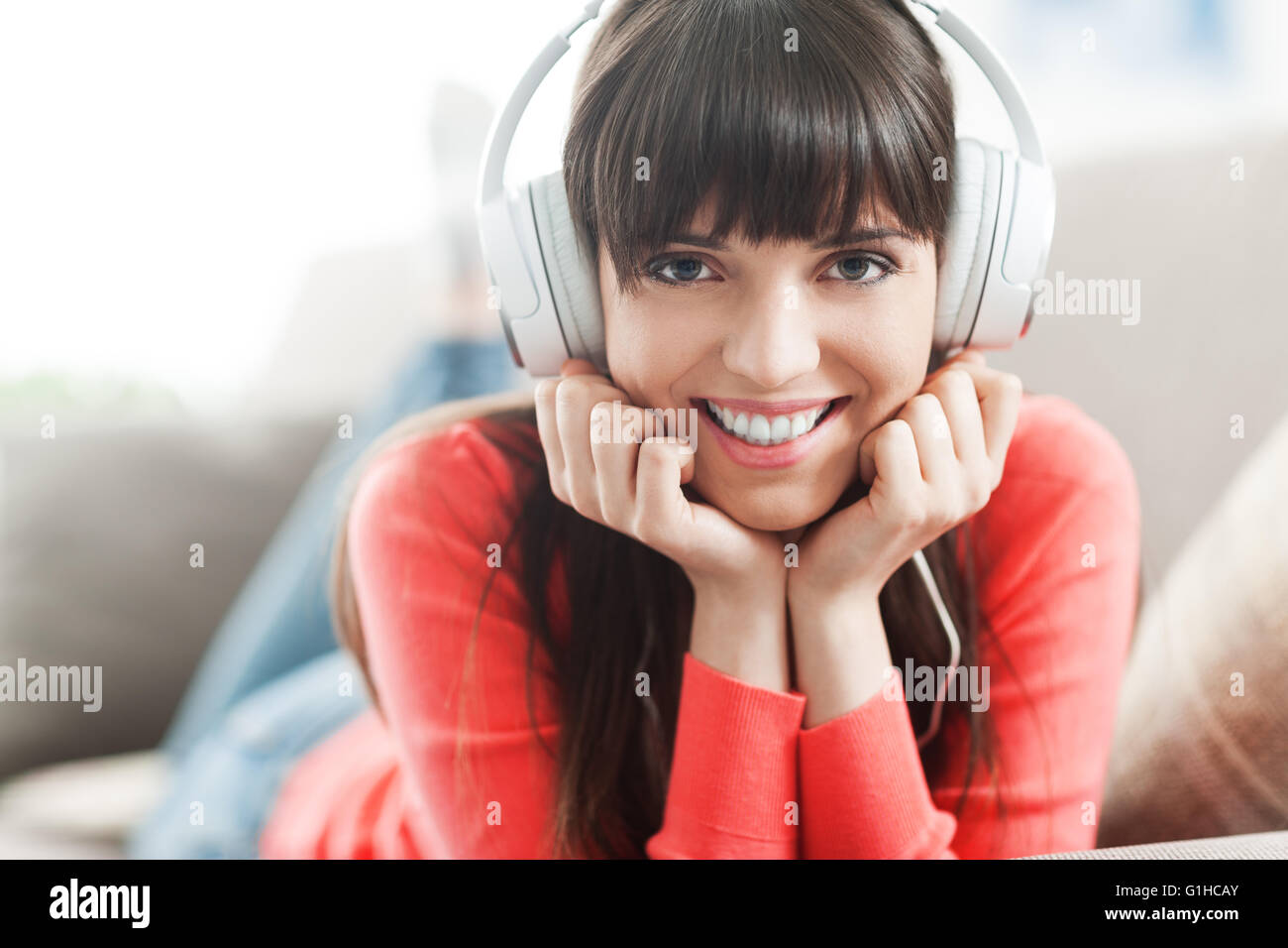 Young smiling woman relaxing and listening to music with headphones - Stock Image