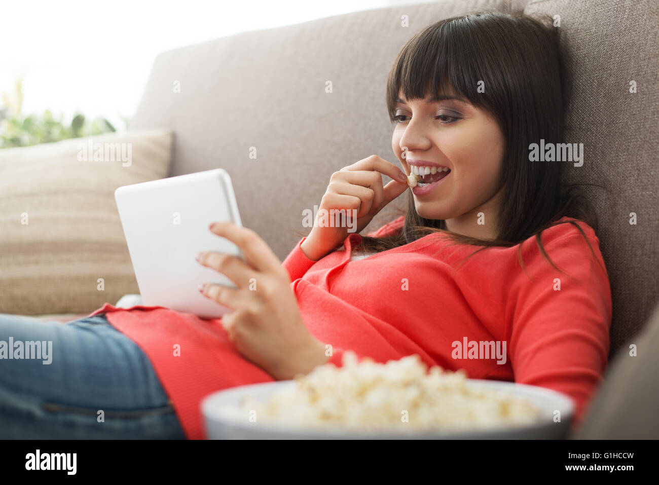 Attractive woman relaxing on the couch at home, she is watching videos online and eating popcorn, movies streaming - Stock Image