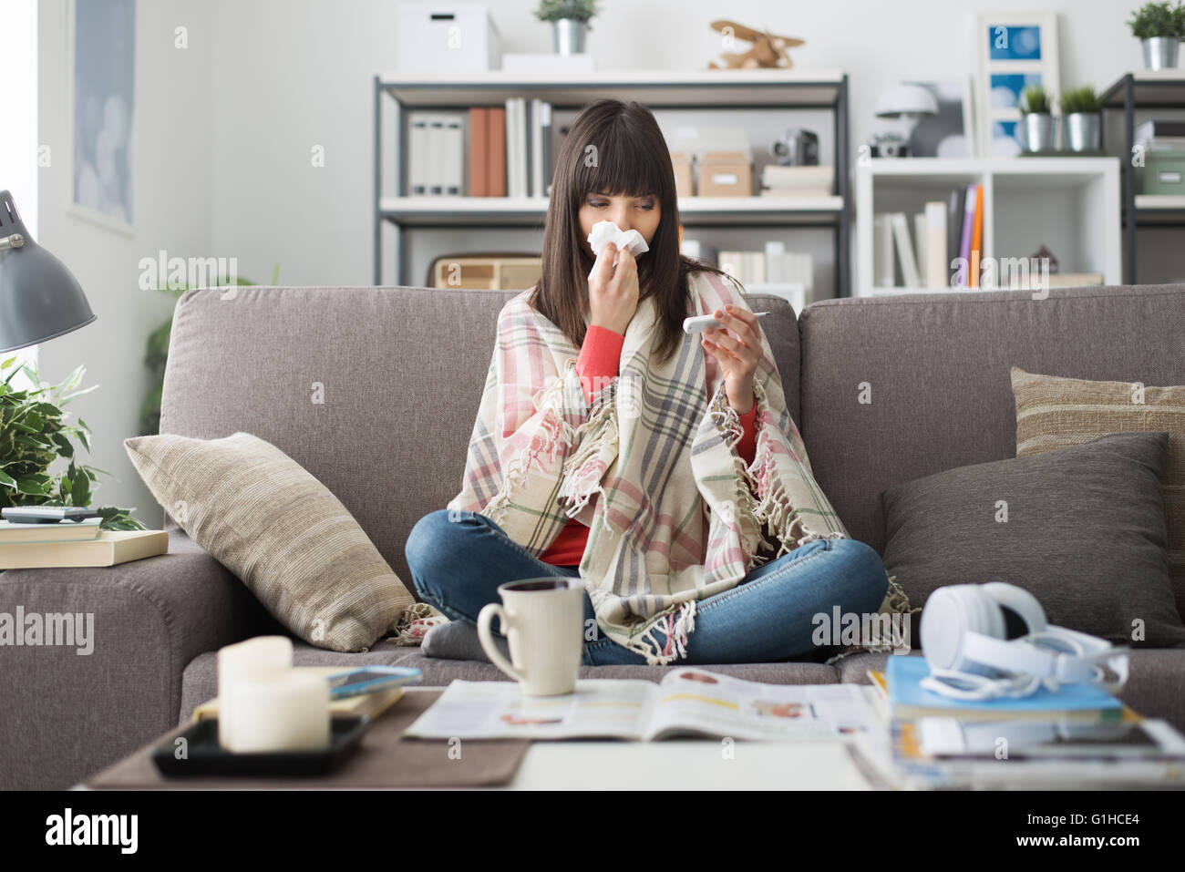 Sick woman with cold and flu, she is resting on the sofa at home and measuring body temperature with a thermometer - Stock Image