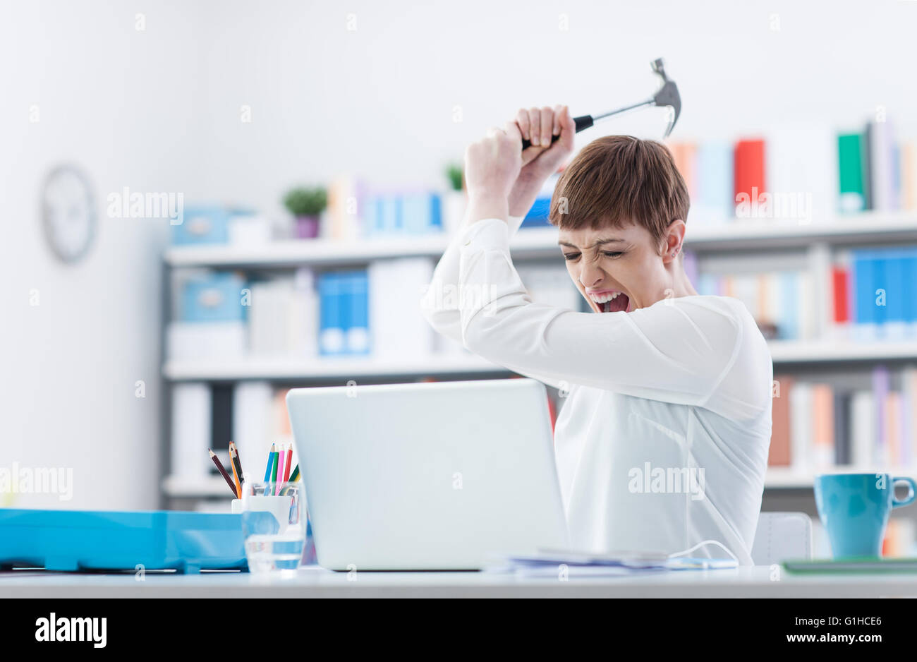 Stressed woman screaming and destroying her laptop with an hammer, computer problems and overwork concept - Stock Image