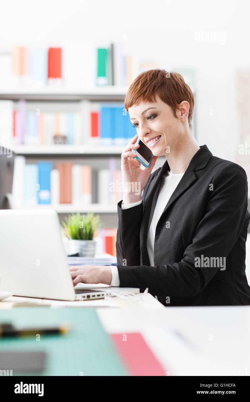 Smiling confident businesswoman on the phone, she is calling with a smart phone and sitting at office desk - Stock Image
