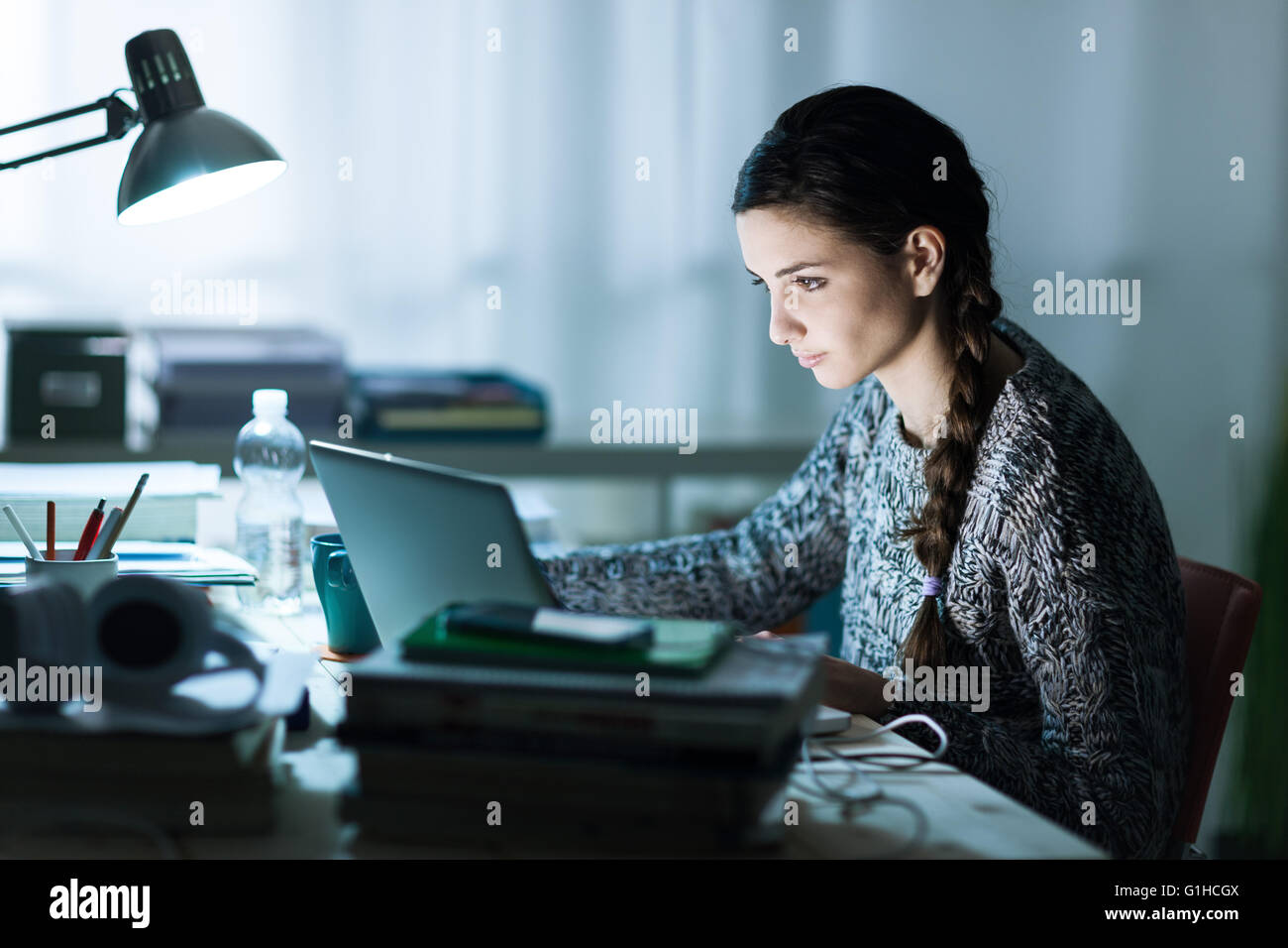 Pretty young student sitting at desk and doing her homework, she is connecting to the internet with a laptop - Stock Image