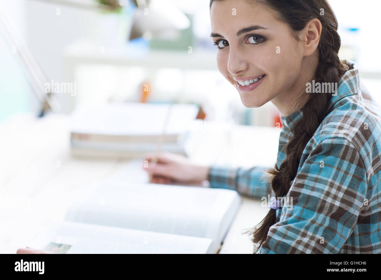 Smiling young student girl studying and reading a book, education and learning concept - Stock Image