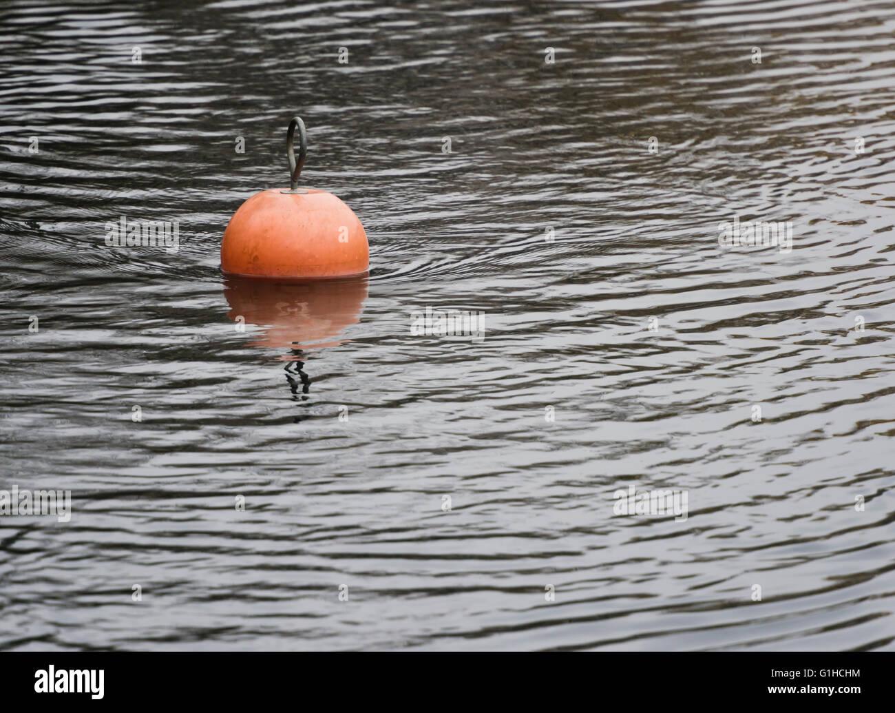 Bright orange nautical buoy floating on slightly rippled water surface - Stock Image