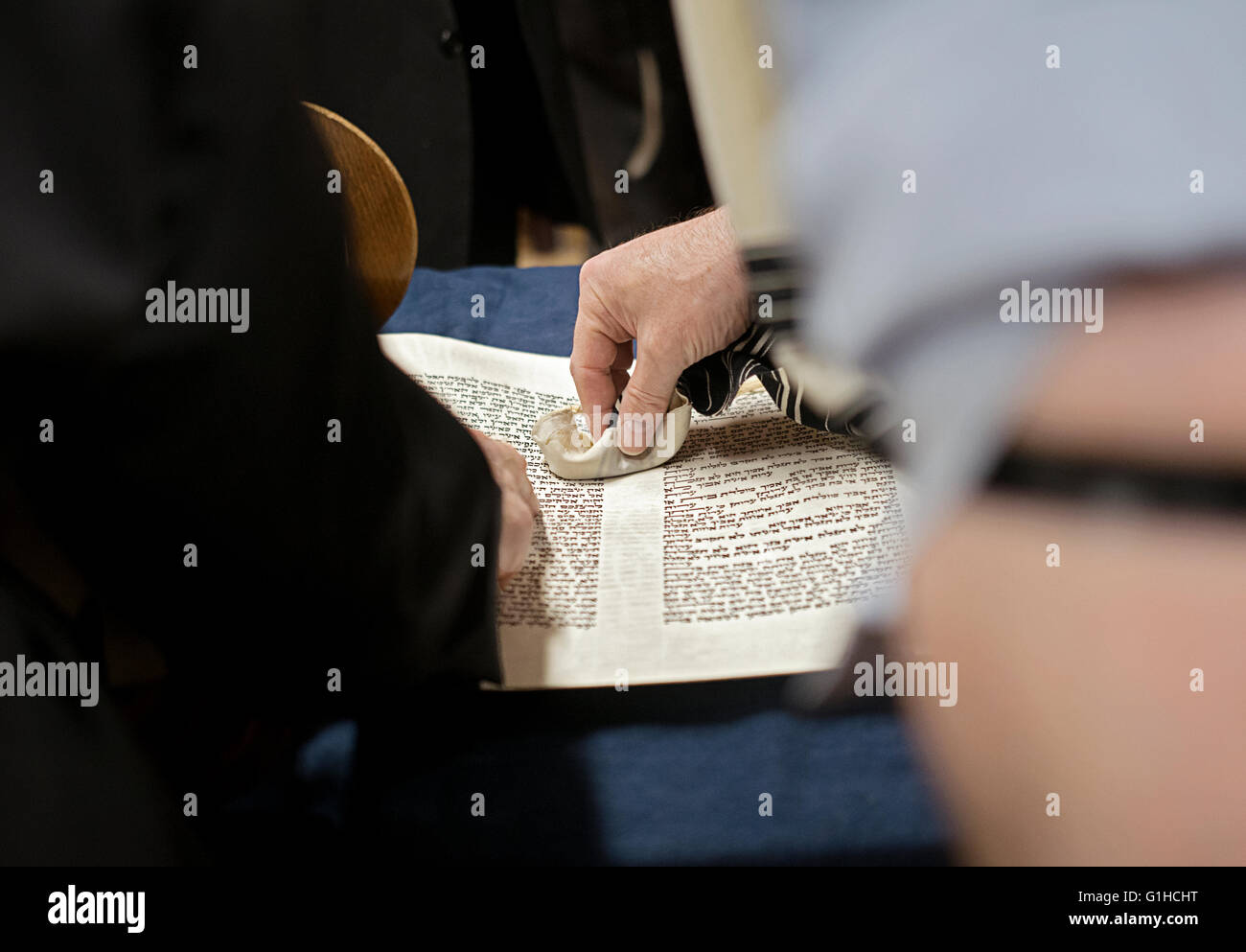 A religious Jewish man touches a spot where a Torah reading will begin when he is called up for a blessing. Brooklyn, - Stock Image