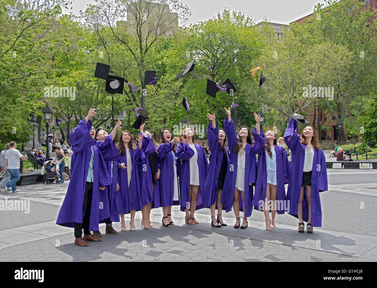 Asian NYU graduates throw their caps in the air for a graduation group photo in Washington Square Park in New York - Stock Image