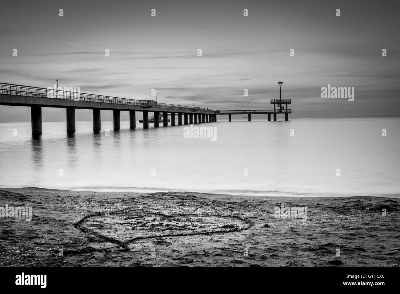 Sunrise over a sea bridge. Heart drawn in the sand. - Stock Image