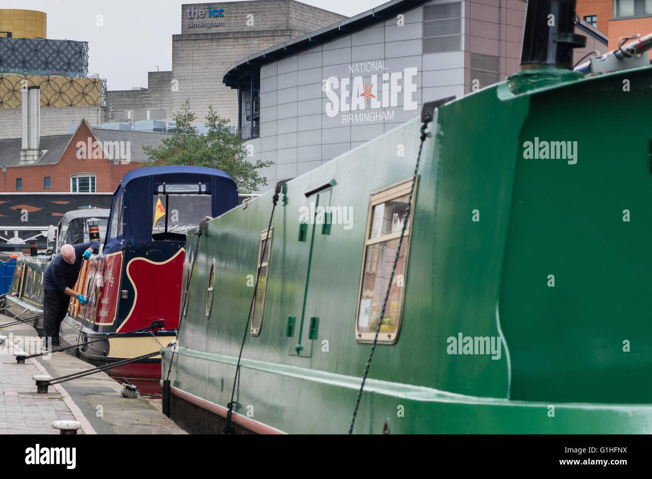 A man cleans his narrowboat on the Birmingham Canal Old Line, close to the city centre and near National Sea Life, - Stock Image