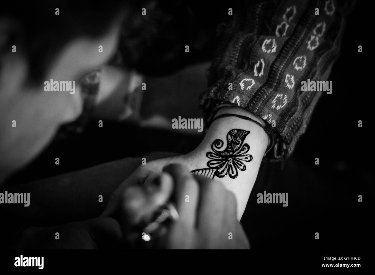 A Boy Is Painting A Mehndi Henna Tattoo Onto The Forearm Of A