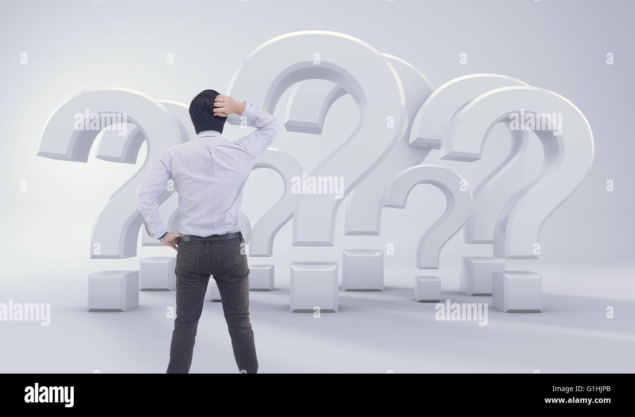 Asian Man Standing In Front of Big Question Mark - Stock Image