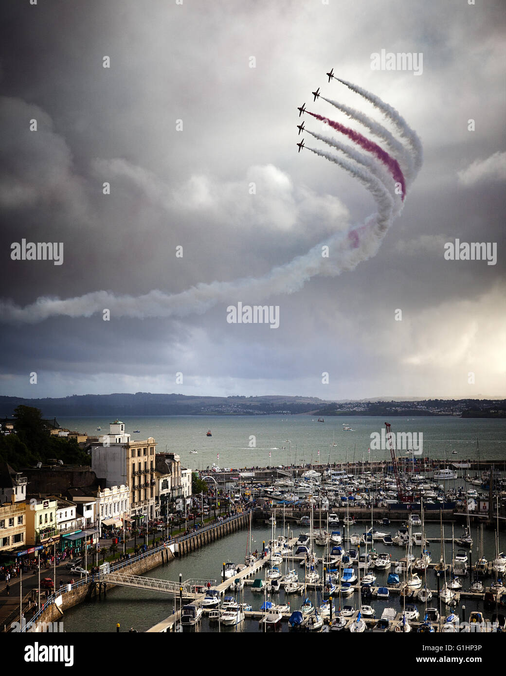 GB - DEVON: Red Arrows Royal Airforce Aerobatic Team above Torbay (Torquay Harbour in foreground) Stock Photo